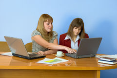 Girls work sitting at a table Stock Photo