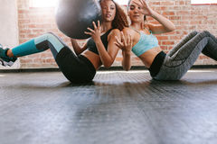 Girls working out in gym with medicine ball. Two young women exercising with medicine ball in gym. Girls working out in gym Royalty Free Stock Photography