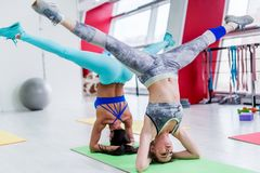 Girls working out together doing wide leg headstand, advanced yoga pose in modern fitness club.  stock photo