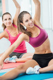 Girls at workout class. Smiling happy girls doing stretching exercises during a class at the gym, fitness and workout concept Stock Image