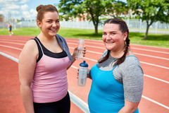 Girls after workout. Two happy females with water refreshing after physical exercises Royalty Free Stock Image