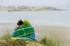 Girls wrapped in blanket on beach Royalty Free Stock Images