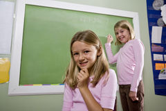 Girls writing on blackboard in classroom Stock Images