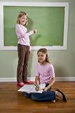 Girls writing on blackboard and doing homework Stock Image