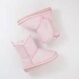 Girls& x27; stivali di inverno su fondo bianco Fotografie Stock Libere da Diritti