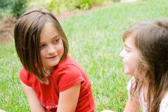 Girls in Yard Talking. Sisters sitting in the grass having a conversation royalty free stock images