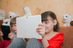 Girls 5 and 7 years old playing tablets Royalty Free Stock Photography