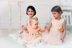 Three sisters poising in beautiful dresses stock photo