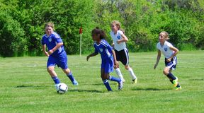 Girls youth soccer players race to the goal. stock images
