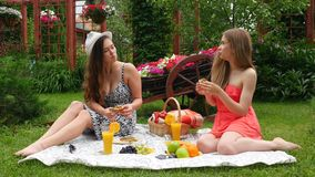 GirlsEating during Picnic. 2 Girls Have A Picnic In A Garden, On A Beautiful Spring Day stock video