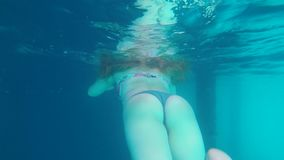 Girlwith beautiful booty diving in water, tourist enjoys day recreation at sea relaxation actively swims in blue water. Girl with beautiful booty diving in water stock video footage