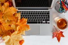 Girly Bürodesktop mit leerem weißem Laptopschirm, Blumen, Kaffee, Smartphone und verschiedenen Bürowerkzeugen Spott oben Stockfotografie