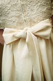 Girly Bow. A large bow tied on a girls off white dress Stock Photos
