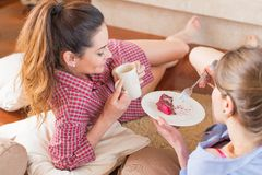 Girly chitchatting. Girlfriends talking near a cup of coffee and cake Stock Photo