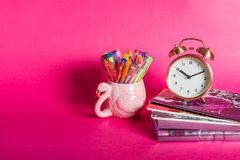 Girly Desk table or Office settings. Back to school concept. Different Notebooks, alarm clock and flamingo mug with colorful gel pens and stationery on bright royalty free stock photo