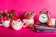 Girly Desk table or Office settings. Back to school concept. Different Notebooks, alarm clock, unicorn mug, lip balm and flamingo mug with colorful gel pens on stock photo
