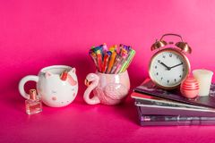 Girly Desk table or Office settings. Back to school concept. Different Notebooks, alarm clock, unicorn mug, lip balm and flamingo mug with colorful gel pens on stock images
