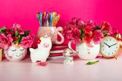 Girly Desk table or Office settings. Back to school concept. Different Notebooks, alarm clock, unicorn mug, llama squishy, Alstroemeria flowers and flamingo mug royalty free stock photography