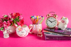 Girly Desk table or Office settings. Back to school concept. Different Notebooks, alarm clock, unicorn mug, llama squishy, and flamingo mug with colorful gel royalty free stock photo