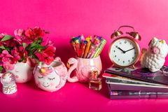 Girly Desk table or Office settings. Back to school concept. Different Notebooks, alarm clock, unicorn mug, llama squishy, and flamingo mug with colorful gel royalty free stock image