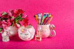 Girly Desk table or Office settings. Back to school concept. Unicorn mug, angel glass ball, and flamingo mug with colorful gel pens and stationery on bright pink stock images