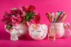 Girly Desk table or Office settings. Back to school concept. Unicorn mugs with Alstroemeria Flowers and flamingo mug with colorful gel pens on bright pink royalty free stock photos