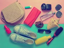 Girly fashionable spring and summer accessories. Sneakers, cosmetics, beauty and hygiene products, a bag, sunglasses on a pink blue pastel background. What&# Stock Photos