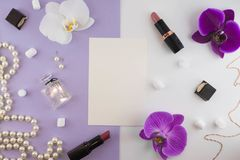 Girly flat lay background. Violet paper background with lipstick, perfume, orchids and jewelry.  stock photography