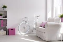 Girly interior with white, stylish bike. Light interior with handmade wood bookcase, sofa and white bike Royalty Free Stock Photography