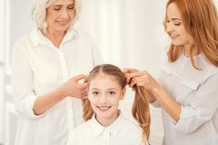 Loving granny and mother combing hair of charming granddaughter. Girly moments. Adorable little girl smiling into the camera while sitting on a chair and waiting Stock Photo