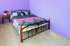 Girly room. Girly bedroom with floral sheets and purple wall Stock Photos