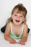 Girly Smile. A little girl lying on her stomach smiling Stock Photography