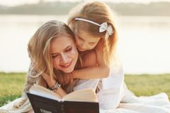 Girly tries to read that fast. Mom and daughter reading a book in a sunny day laying on the grass with lake at
