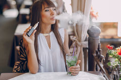 Girn en café con el E-cigarrillo Foto de archivo libre de regalías