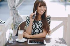 Girn en café con el E-cigarrillo Imagen de archivo libre de regalías