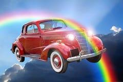 Giro classico d'annata dell'automobile di fantasia attraverso le nuvole dell'arcobaleno royalty illustrazione gratis