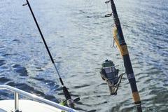 Giro con la pesca con cebo de cuchara con cebo de cuchara en el casco del ` s de la nave contra el fondo imagen de archivo