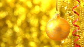 Giro de oro de la bola de la Navidad Decoración del Año Nuevo Bokeh de oro borroso 00183f almacen de metraje de vídeo