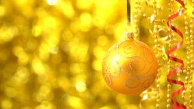 Giro de oro de la bola de la Navidad Decoración del Año Nuevo Bokeh de oro borroso que brilla tenuemente almacen de metraje de vídeo