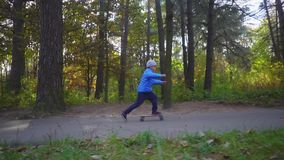 Giro del bambino del ragazzo del skateboarder sul pattino all'aperto nel parco di autunno