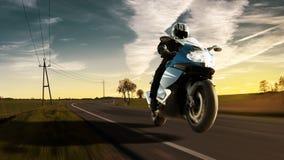 Giro del motociclo sulla strada campestre con il cielo d'imposizione ed il tramonto immagine stock libera da diritti