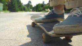 Giro del ragazzo del pattinatore sul pattino nel parco del pattino all'aperto Scarpe arancio di usura del piede del pattino, piat video d archivio