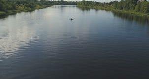 Giro del ragazzo in una barca a remi su un lago stock footage