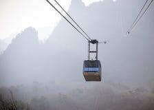 Giro della cabina di funivia fino alle montagne Fotografia Stock