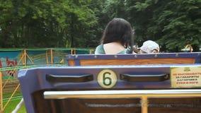 Giro della gente nelle attrazioni del parco le montagne russe stock footage