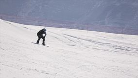 Giro dello Snowboarder nel pendio, salto dal trampolino Stazione sciistica attività Montagna stock footage
