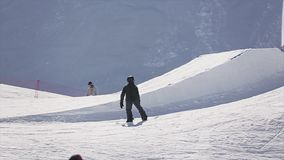 Giro dello Snowboarder nel pendio, salto dal trampolino Stazione sciistica Mani di aumento sunny video d archivio