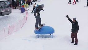Giro dello Snowboarder sull'estrattore a scatto alla stazione sciistica in montagne Sport estremo La gente prodezze cineoperatore archivi video