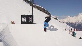 Giro dello Snowboarder sulla palla del tiro del trampolino nel canestro di pallacanestro La gente ricorso video d archivio
