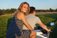 Giro di divertimento Giovani coppie che guidano una motocicletta Tipo bello e donna graziosa sul motociclo Giovani cavalieri che  Fotografia Stock